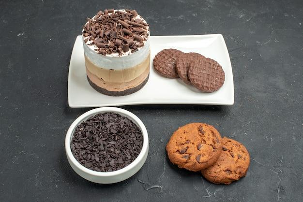 Bolo de chocolate de vista frontal e biscoitos em uma tigela de prato retangular branco com biscoitos de chocolate amargo no fundo escuro isolado