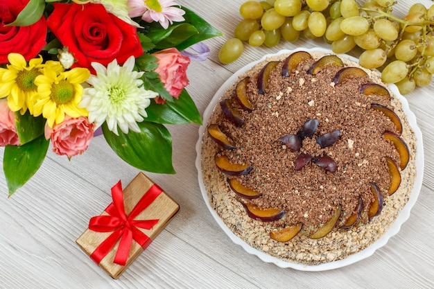 Bolo de chocolate decorado com ameixas, um buquê de flores, uvas e uma caixa de presente nas placas de madeira cinza.