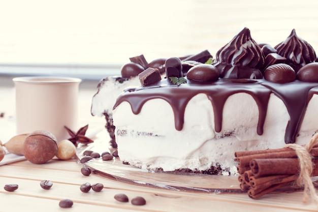Bolo de chocolate decorado com chocolates com nozes de macadâmia e uma xícara de café
