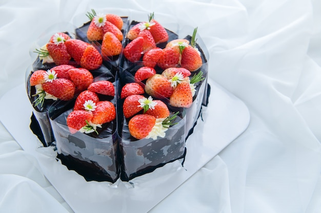 Bolo de chocolate decorado com morango fresco em um pano branco, bolo e conceito de padaria Foto Premium