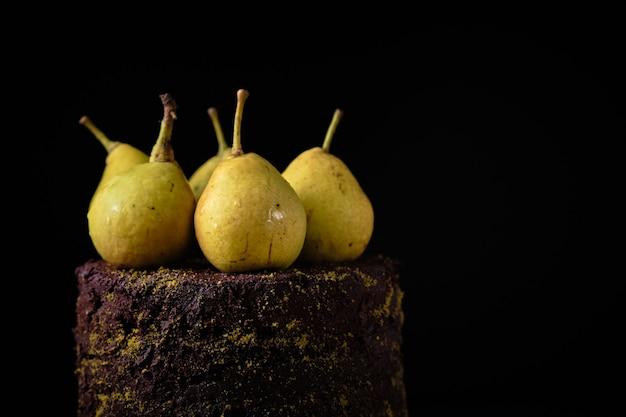 Bolo de chocolate decorado com pistache moído e peras frescas em uma placa de madeira.