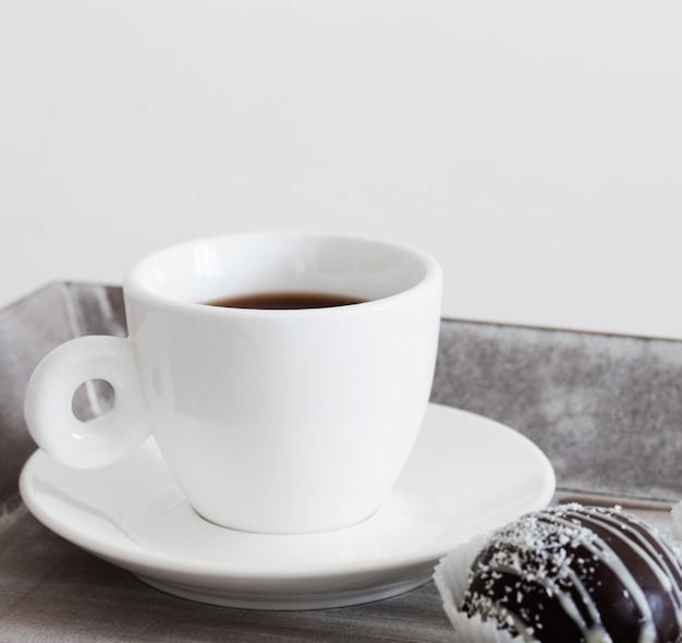Bolo de chocolate doce com copo na bandeja de madeira