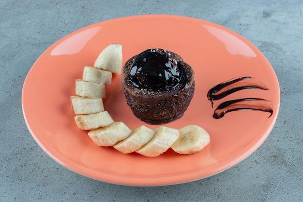 Bolo de chocolate doce com rodelas de banana.