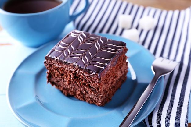 Bolo de chocolate doce em prato azul com uma xícara de chá na mesa de madeira