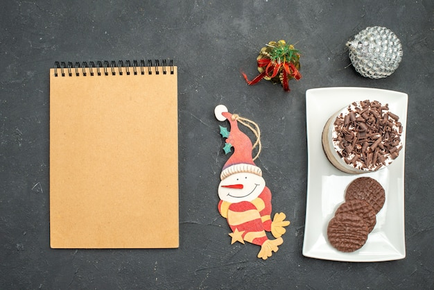 Bolo de chocolate e biscoitos em uma placa retangular branca. a árvore de natal brinca com um caderno no fundo escuro e isolado.