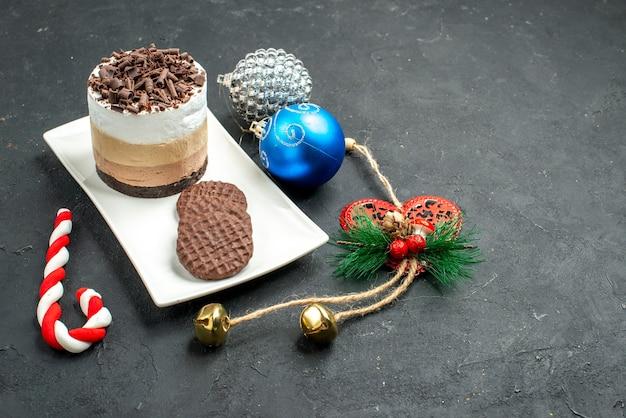 Bolo de chocolate e biscoitos em uma placa retangular branca de frente para a árvore de natal, brinquedos coloridos em um lugar escuro e livre