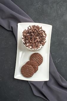Bolo de chocolate e biscoitos em uma placa retangular branca xale roxo em fundo escuro isolado.