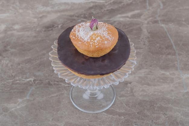 Bolo de chocolate e bolo com cobertura em pó de baunilha empilhados em um pedestal de vidro sobre mármore