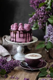 Bolo de chocolate e um buquê de lilases na mesa de madeira