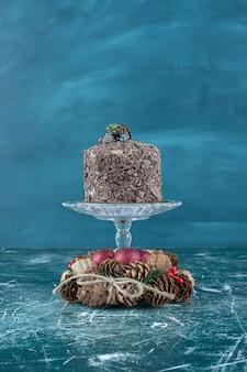 Bolo de chocolate em um pedestal e uma coroa de pinha em azul.