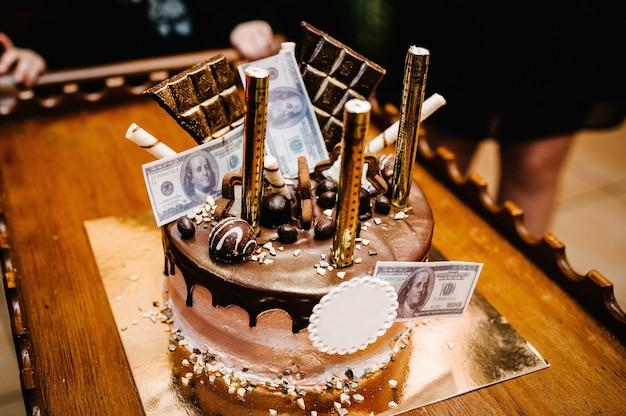 Bolo de chocolate festivo decorado com velas de ouro e dinheiro.