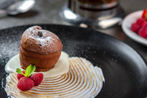 Bolo de chocolate fondant com creme de baunilha, framboesa e hortelã em um prato preto