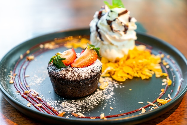 Bolo de chocolate lava com sorvete de morango e baunilha em prato preto