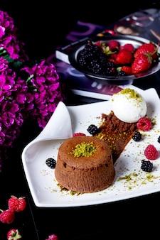 Bolo de chocolate pequeno decorado com pistache, servido com sorvete de baunilha