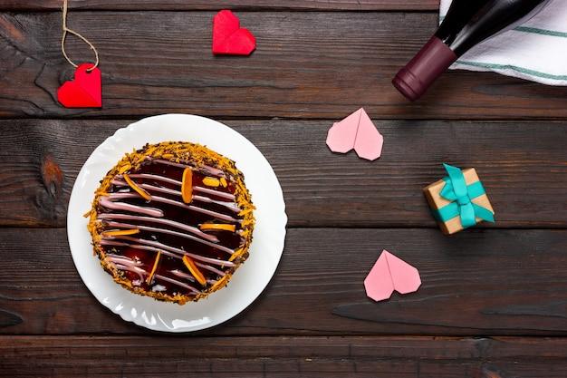 Bolo de chocolate, pequenos corações de papel e uma garrafa de vinho em uma mesa de madeira escura.