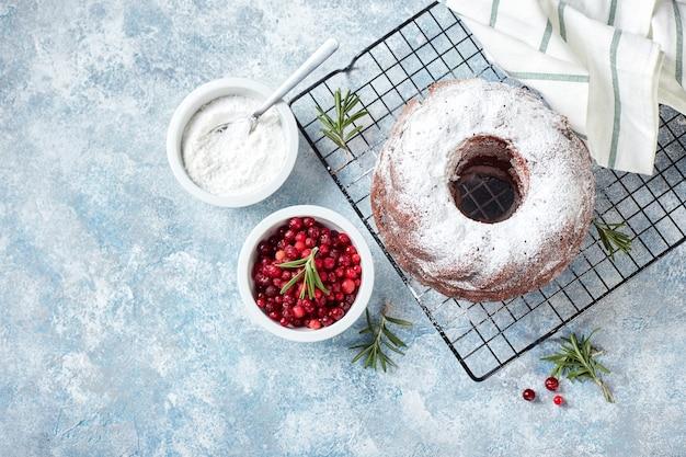 Bolo de chocolate polvilhado com açúcar de confeiteiro em uma gradinha de metal, açúcar de confeiteiro e cranberries em tigelas, preparado para decoração.
