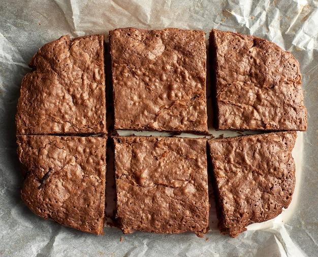 Bolo de chocolate retangular cozido brownie com superfície rachada em papel pergaminho branco
