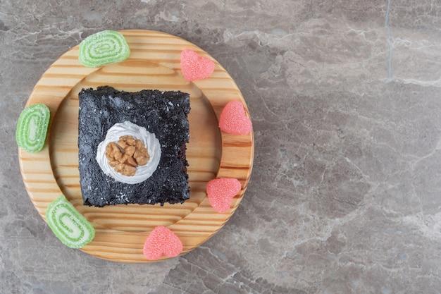 Bolo de chocolate rodeado de geleias em uma travessa sobre superfície de mármore