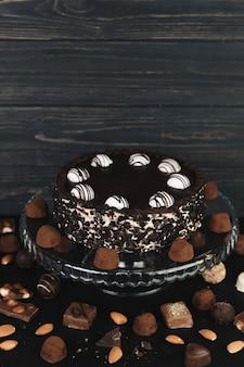 Bolo de chocolate rodeado por trufas de chocolate e bombons