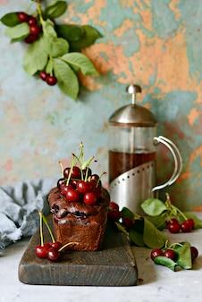 Bolo de chocolate saboroso (brownie) com cereja em uma placa de madeira.