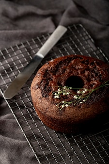 Bolo de chocolate sobre um fundo cinza com uma faca
