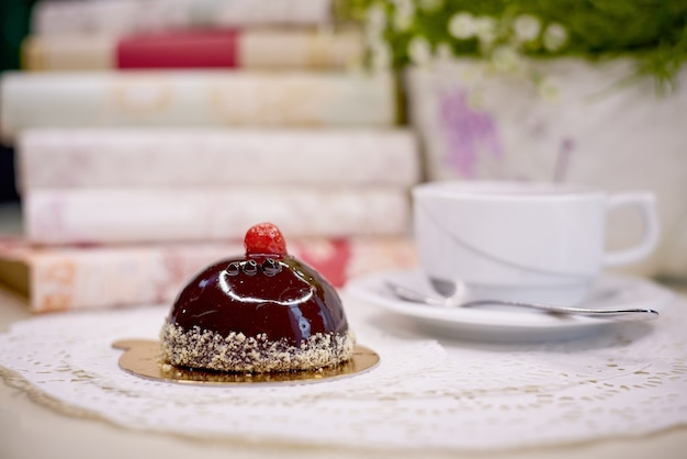 Bolo de cobertura de chocolate com chá em uma mesa com flores e livros.