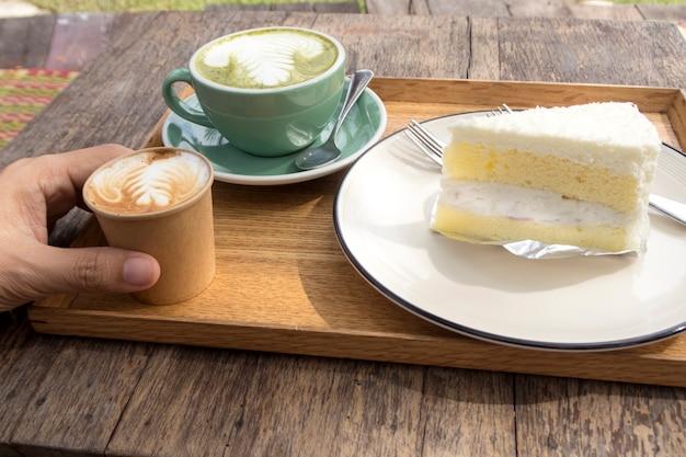 Bolo de coco e chá quente chá matte e café em mesa de madeira.