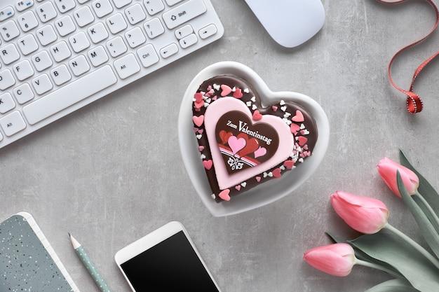 Bolo de coração dia dos namorados com texto na mesa com dispositivos eletrônicos e tulipas
