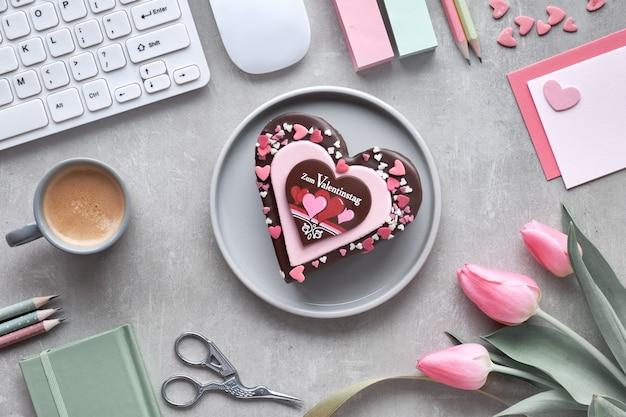 Bolo de coração dia dos namorados na mesa com teclado, café, cartões e tulipas cor de rosa