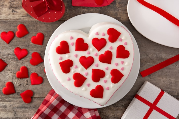 Bolo de coração para o dia dos namorados decorado com corações de açúcar na mesa de madeira