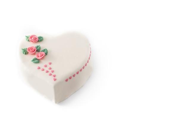 Bolo de coração para o dia dos namorados, decorado com rosas e corações rosa de açúcar isolados no fundo branco