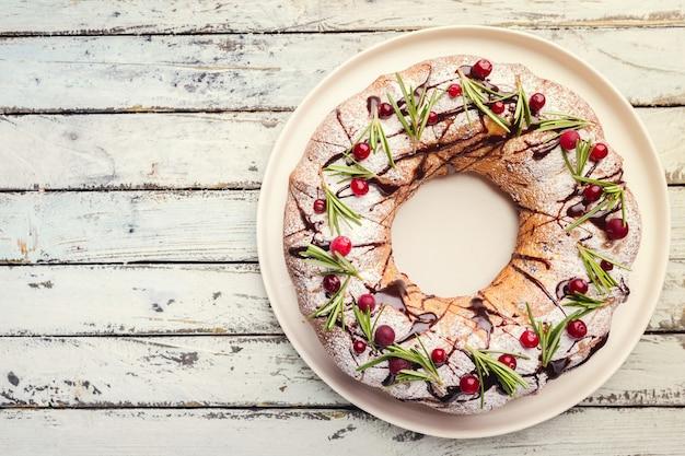 Bolo de cranberries bundt com chocolate e laranja em um prato branco. sobremesa caseira de outono e inverno aconchegante em uma mesa de madeira rústica, vista superior