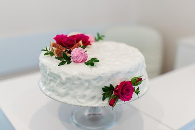 Bolo de creme branco decorado com rosas vermelhas.
