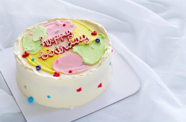 Bolo de creme de manteiga de cor pastel na superfície de pano branco, feliz dia de nascimento e conceito mínimo de bolo