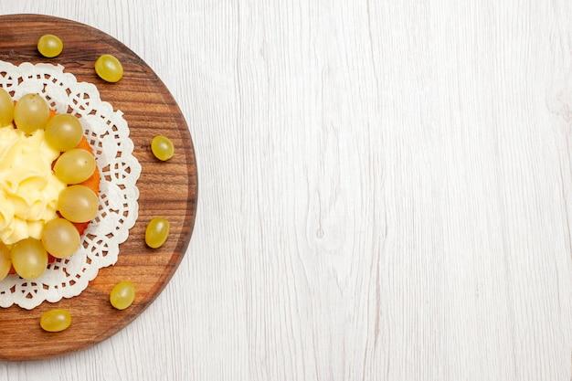 Bolo de creme de vista de cima com uvas frescas em um biscoito de torta de bolo de frutas de mesa branca