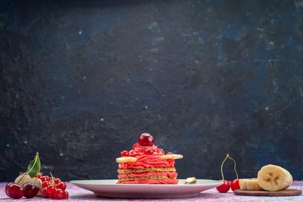 Bolo de creme vermelho de vista frontal dentro de um prato branco com frutas frescas no escuro