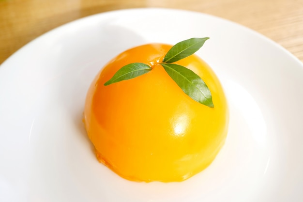 Bolo de cúpula de mandarina cor vívida em um prato branco