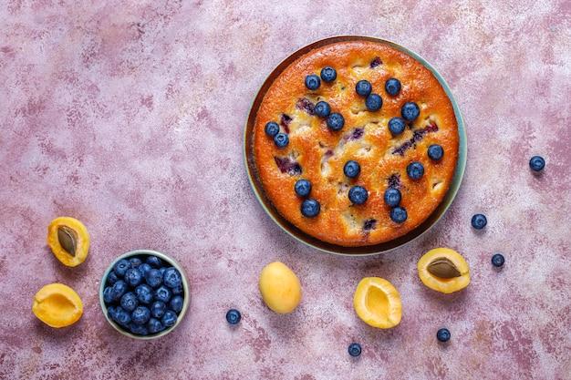 Bolo de damasco e mirtilo com mirtilos frescos e frutas de damasco