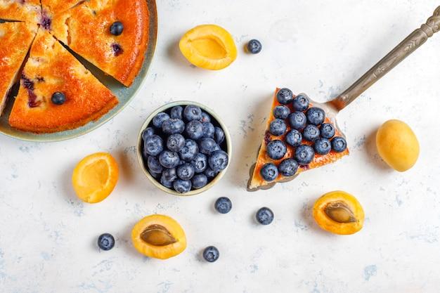 Bolo de damasco e mirtilo com mirtilos frescos e frutas de damasco.