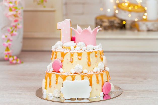 Bolo de duas camadas para o primeiro aniversário. em cima do bolo o número 1 e o papelão.