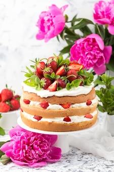 Bolo de esponja com creme branco e morangos em um carrinho do bolo