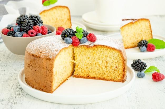 Bolo de esponja de baunilha clássico caseiro ou biscoito polvilhado com açúcar de confeiteiro e frutas frescas em um prato branco