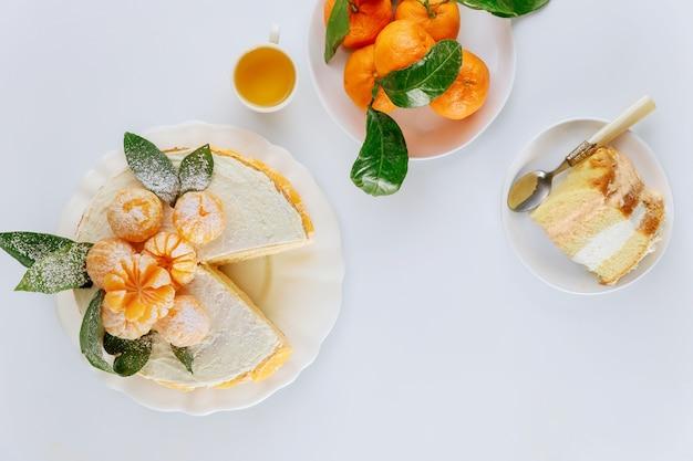 Bolo de esponja de tangerina pedaço decorado com tangerinas inteiras frescas.