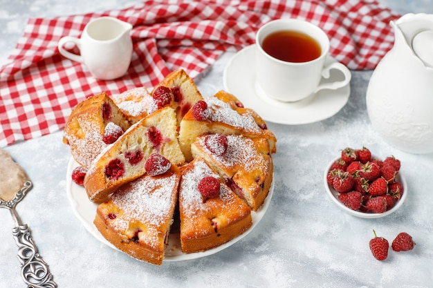 Bolo de framboesa com açúcar em pó e framboesas frescas em uma luz. sobremesa de verão berry.