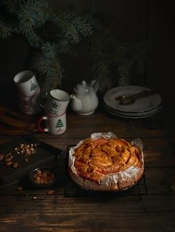 Bolo de frutas, canecas de chá, galhos de árvores de natal