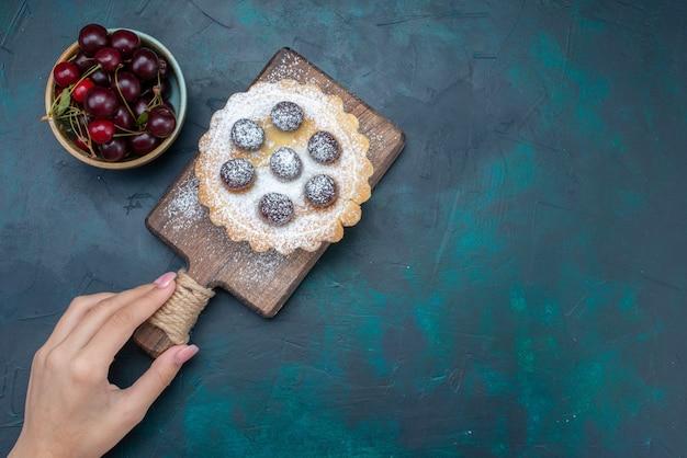 Bolo de frutas com açúcar em pó e cerejas ácidas em fundo azul escuro