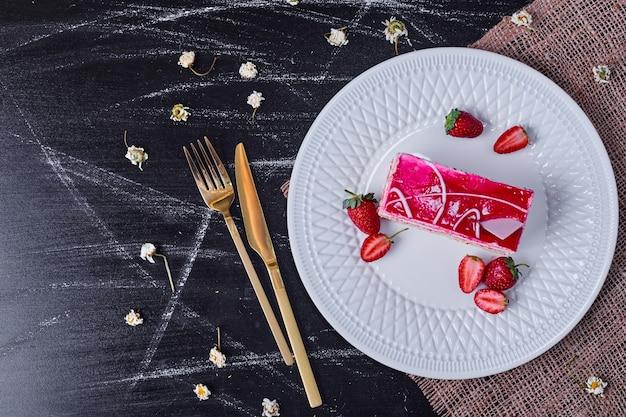 Bolo de frutas com morangos em um prato branco com talheres de ouro.