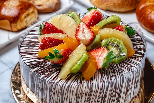 Bolo de frutas de vista lateral com creme de baunilha, chocolate, kiwi, laranja, abacaxi e morango