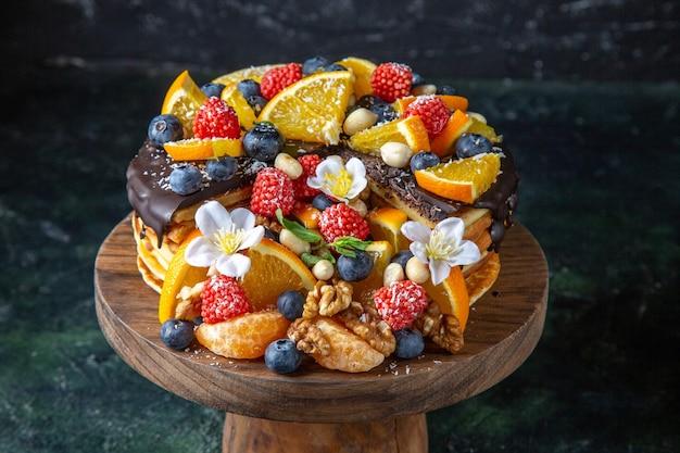 Bolo de frutas delicioso com calda de chocolate em mesa redonda de madeira escura