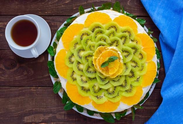 Bolo de frutas festivo redondo brilhante decorado com kiwi, laranja, menta e uma xícara de chá.